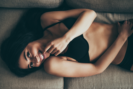 beautiful nude woman: Feeling playful. Top view of playful young mixed race woman in black lingerie looking at camera and touching lips with finger while lying on couch