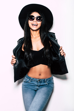 expressing positivity: Enjoying her style. Beautiful young mixed race woman in leather jacket and hat posing against white background and expressing positivity