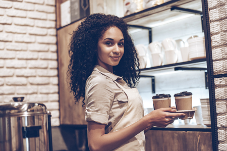 best coffee: Best coffee in this city! Young cheerful African woman in apron holding coffee cups and looking at camera with smile while standing at cafe