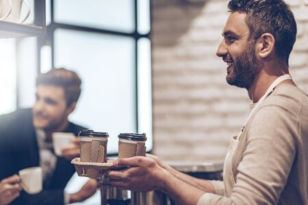 standing businessman: Your coffee to go! Side view of barista passing coffee cups to his customer with smile while standing at bar counter