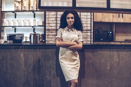 dueño del café confiado. mujer africana joven alegre en el delantal de mantener los brazos cruzados y mirando a cámara con una sonrisa mientras se está en la barra del bar