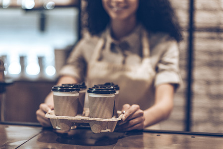 best coffee: Best coffee to go! Part of young cheerful African woman in apron holding coffee cups while standing at cafe
