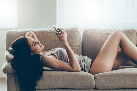 beautiful sex: Typing message to him. Beautiful young woman in panties and tank top holding smart phone and looking at it with smile while lying on couch at home