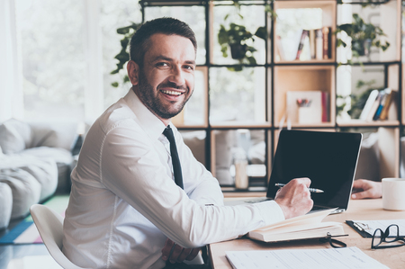 looking at computer: Always ready to help you. Confident mature man in shirt and tie looking at camera and smiling while sitting at his working place in office