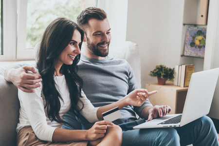 man and women: Choosing what to get. Beautiful young woman holding credit card and pointing laptop with smile while sitting together with her husband on the couch