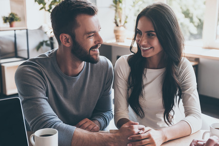 feeling happy: Feeling happy now. Happy young loving couple holding hands and looking at each other while sitting at the desk with some man sitting in front of them