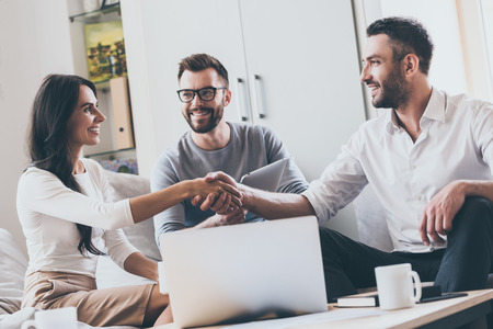 working with hands: Welcome on board! Three young cheerful business people sitting together at the desk while man and woman shaking hands Stock Photo