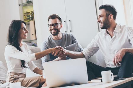 Willkommen an Bord! Drei junge fröhliche Geschäftsleute, die zusammen sitzen am Schreibtisch, während Mann und Frau die Hände schütteln