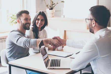 Good deal! Cheerful young man bonding to his wife while shaking hand to man sitting in front of him at the desk Archivio Fotografico