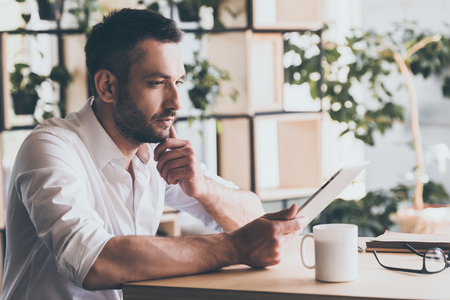 mature man: Surfing web in cafe. Side view of thoughtful young man looking at his digital tablet while sitting in office or cafe