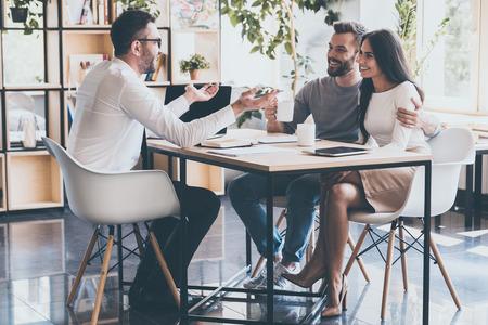 Dobrá zpráva pro vás! Veselý mladý pár, který se navzájem spojí a poslouchá svého finančního poradce, který sedí u stolu před nimi