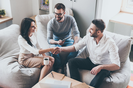 Welcome to team! Top view of three young cheerful business people sitting together at the desk while man and woman shaking hands