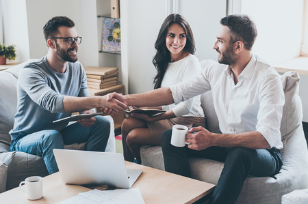 Congratulations! Three young cheerful business people sitting together at the desk while men shaking hands