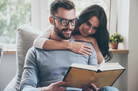 persona leyendo: La lectura de su libro favorito. Hermosa mujer joven unir a su marido mientras él está leyendo un libro en el sofá Foto de archivo