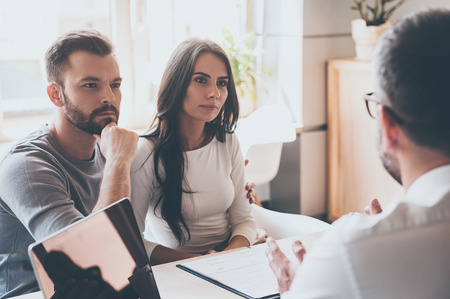 Listening to financial advisor. Concentrated young couple bonding to each other and listening to some man sitting in front of them at the desk in office Stockfoto