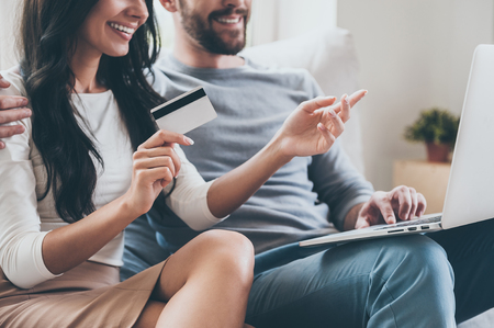 I want this! Close-up of beautiful young woman holding credit card and pointing laptop with smile while sitting together with her husband on the couch