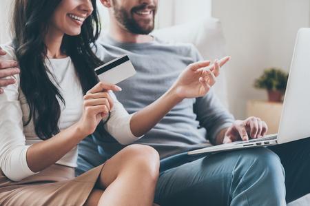 tarjeta de credito: ¡Quiero esto! Primer plano de la hermosa mujer joven que sostiene la tarjeta de crédito y que señala la computadora portátil con una sonrisa mientras se está sentado junto a su marido en el sofá Foto de archivo