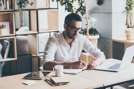 empleado de oficina: Hacer algunas notas. Concentrado hombre maduro escribir algo en el bloc de notas mientras está sentado en su lugar de trabajo en la oficina