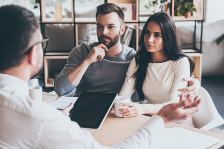 They need expert advice. Young couple sitting together at the desk and listening to their financial advisor Zdjęcie Seryjne - 58177885