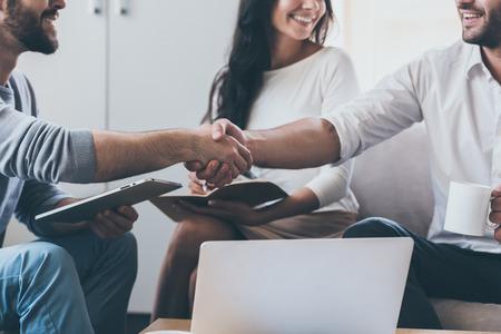 Aangenaam kennis te maken! Close-up van twee jonge zakenlieden handen terwijl de vrouw zitten in de buurt hen en lachend schudden