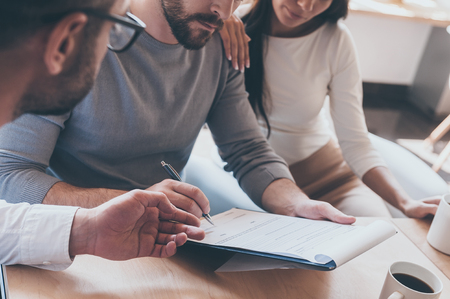 Podepisování dokumentů. Close-up jistý mladý muž podpisu nějaký dokument, zatímco sedí spolu se svou ženou a jiný muž ukázal dokument Reklamní fotografie
