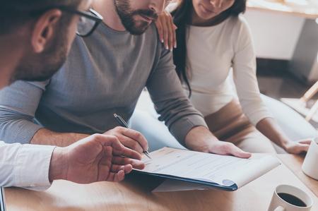 Signieren von Dokumenten. Close-up of zuversichtlich junger Mann ein Dokument unterzeichnen, während zusammen mit seiner Frau sitzt und ein anderer Mann zeigen Dokument