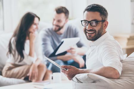 자신감 영업 관리자. 다른 남자와 여자 배경에 앉아있는 동안 명랑 성숙한 남자 디지털 태블릿을 들고 어깨 너머로보고