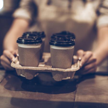 ¡Aqui tienes! Primer plano de una mujer que sirve café para llevar mientras está de pie en el mostrador de la barra de madera Foto de archivo