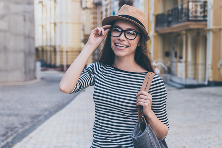 woman bag: Casually beautiful.  Beautiful young woman with bag over shoulder looking at camera and smiling while standing outdoors Stock Photo