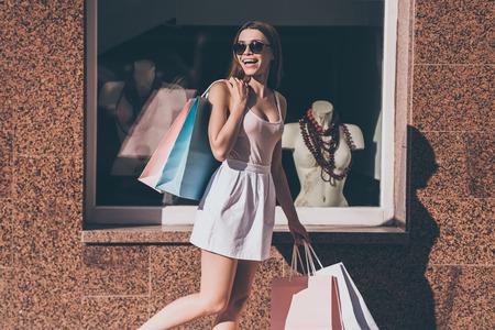 美しいお買いもの。買い物袋を運ぶと背景にあるファッション店と通りを歩きながら笑顔で肩越しに見ている若い美人 写真素材