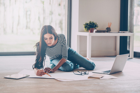 Confident young beautiful woman drawing something on blueprint while sitting on the floor at home Foto de archivo