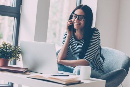 usando computadora: Siempre en contacto. Alegre mujer hermosa joven que trabaja en la computadora portátil y hablando por el teléfono móvil mientras se está sentado en su lugar de trabajo