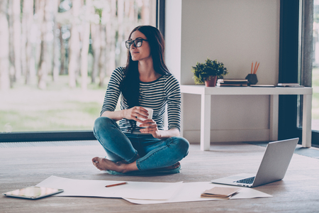 Confident young beautiful woman holding coffee cup and smiling while sitting on the floor at home with blueprint laying near her