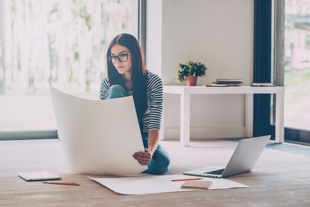 woman sitting with laptop: Having opportunity to work everywhere. Confident young beautiful woman examining blueprint while sitting on the floor at home