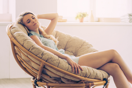 Beautiful young woman keeping eyes closed and holding hand behind head while sitting in big comfortable chair at home