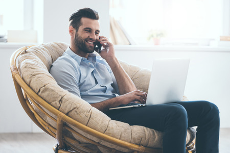 laptop home: Cheerful young handsome man working on laptop and talking on the mobile phone while sitting in big comfortable chair at home