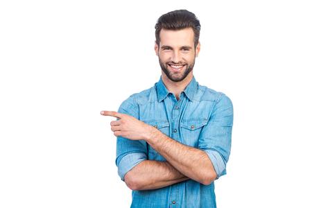 Joven apuesto hombre feliz en la camisa vaqueros señala lejos y sonriendo mientras está de pie contra el fondo blanco Foto de archivo - 58715063