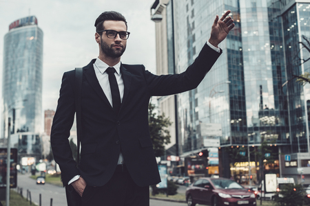catching taxi: Confident young businessman in full suit catching taxi while raising his arm and standing outdoors with cityscape in the background