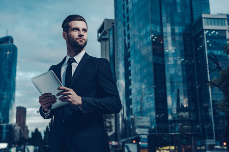 Night time image of confident young man in full suit holding digital tablet and looking away while standing outdoors with cityscape in the background 免版税图像