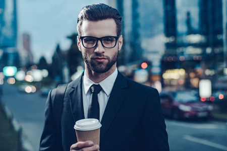 man in suit: Night time image of confident young man in full suit holding coffee cup and looking at camera while standing outdoors with cityscape in the background Stock Photo