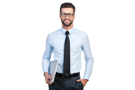 standing businessman: Confident businessman. Confident young handsome man in shirt and tie carrying laptop and looking at camera with smile while standing against white background