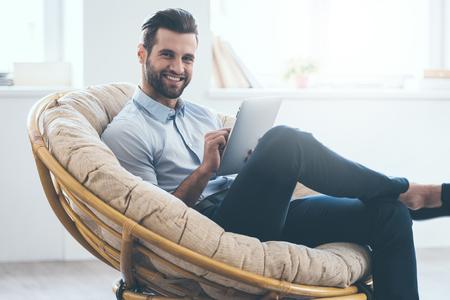 Confiamos joven apuesto hombre trabajando en tableta digital y sonriendo mientras está sentado en una gran silla cómoda en casa