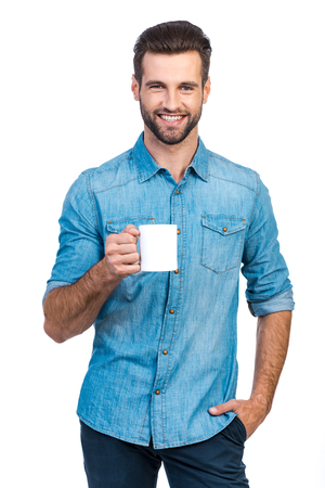 Confident young handsome man in jeans shirt holding cup with hot drink and smiling while standing against white background