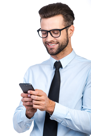 Confident young handsome man in shirt and tie holding mobile phone and looking at it with smile while standing against white background