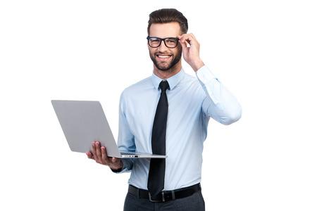 흰색 배경에 서있는 동안 자신감이 젊은 잘 생긴 남자가 셔츠와 노트북을 들고 웃 넥타이