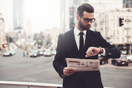urban scene: Confident young man in full suit holding newspaper and looking at his watch while standing outdoors with cityscape in the background
