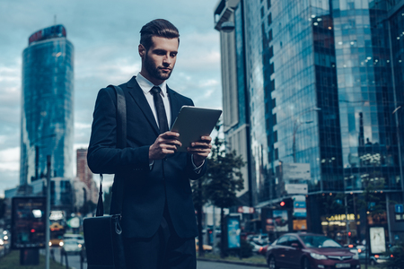 adults: Night time image of confident young man in full suit holding digital tablet and looking at it while standing outdoors with cityscape in the background
