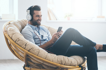 comfortable chair: Handsome young man in headphones looking at his smart phone and smiling while sitting in big comfortable chair at home