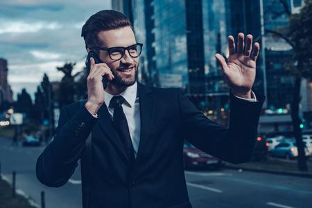 Ya puedo verte! noche la imagen de hombre joven confía en traje completo hablando por teléfono móvil y saludando a alguien mientras está de pie al aire libre con el paisaje urbano en el fondo