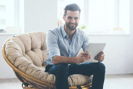 comfortable chair: Confident young handsome man holding digital tablet and smiling while sitting in big comfortable chair at home
